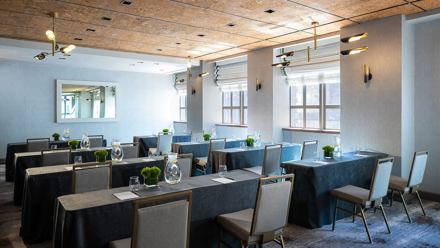 Tyng classroom setup at Kimpton Hotel Palomar Philadelphia showing long tables with notepads on top facing the same direction located next to a wall with large sunlit windows