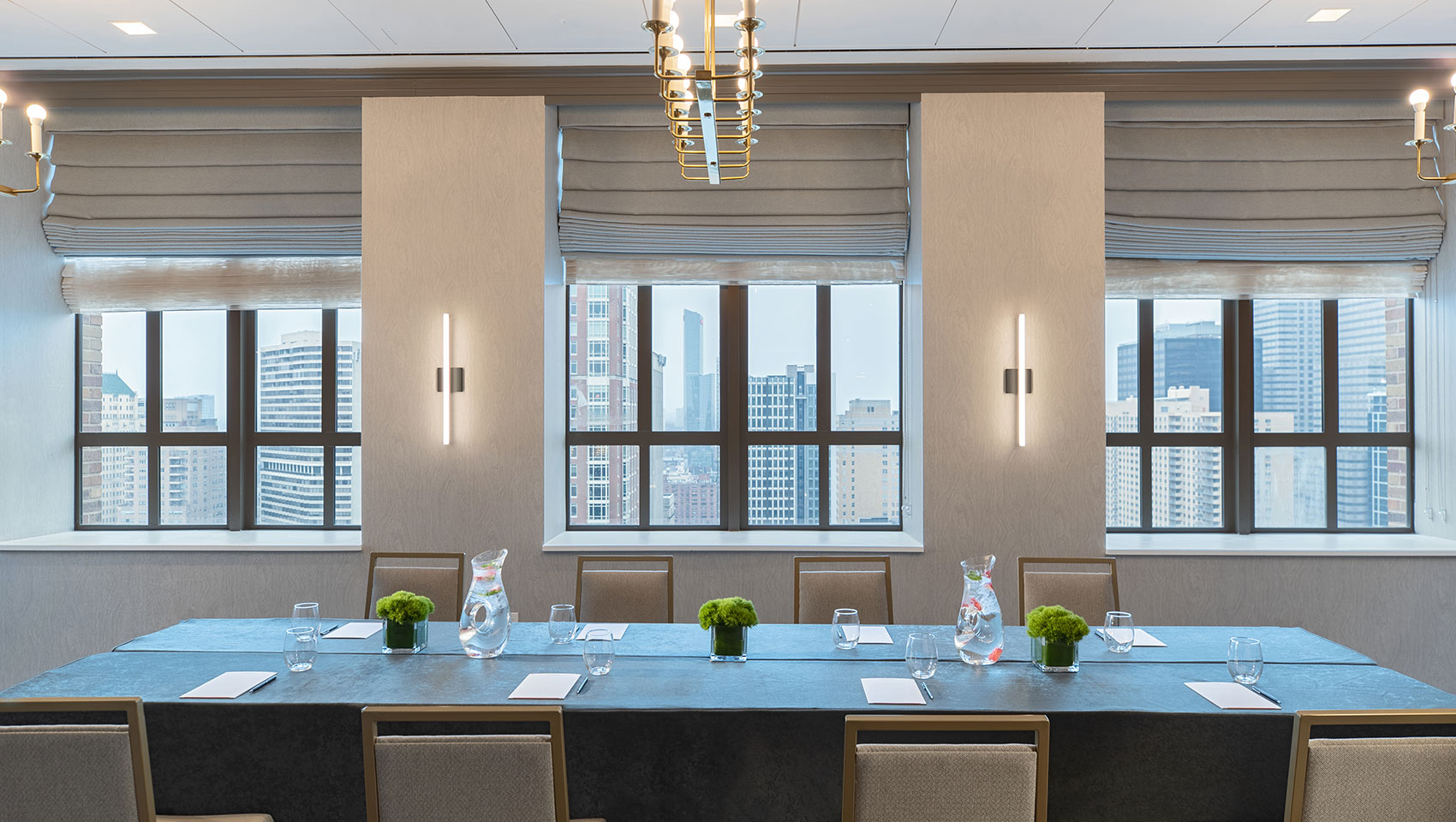 Conference Setup in Abe room located in Kimpton Hotel Palomar Philadelphia showing to long tables with notepads on top surrounded by chairs and large windows on the back wall that overlook city views