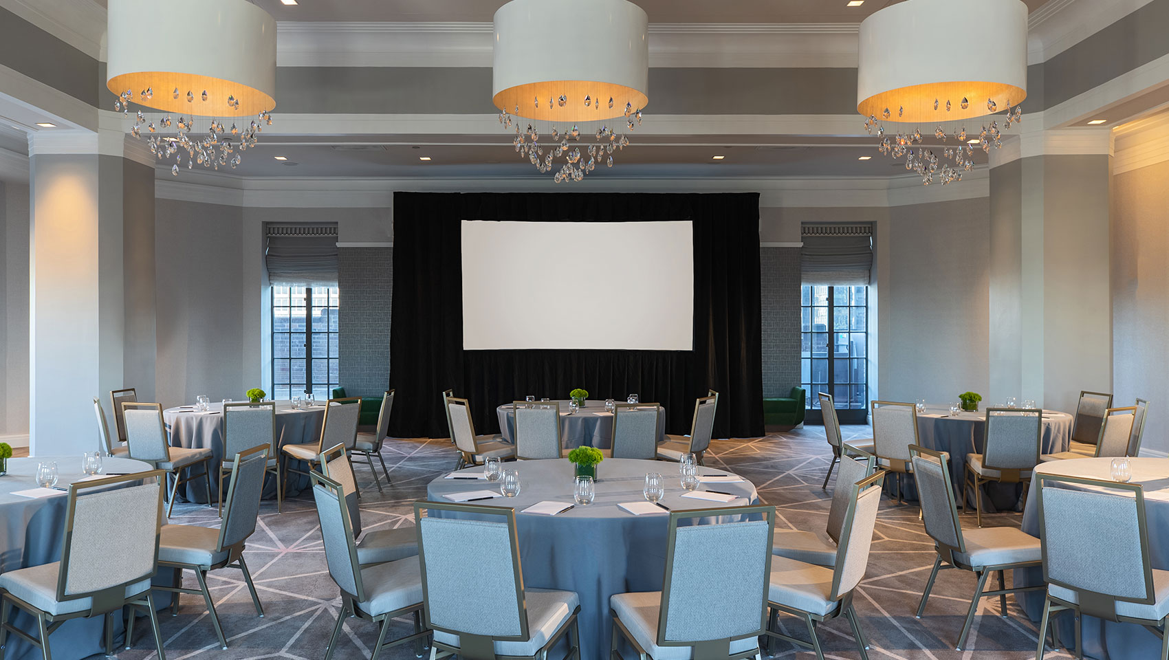 Kimpton Hotel Palomar Philadelphia ballroom with crescent round tables all situated behind a projector screen and underneath 3 identical, circular lighting fixtures