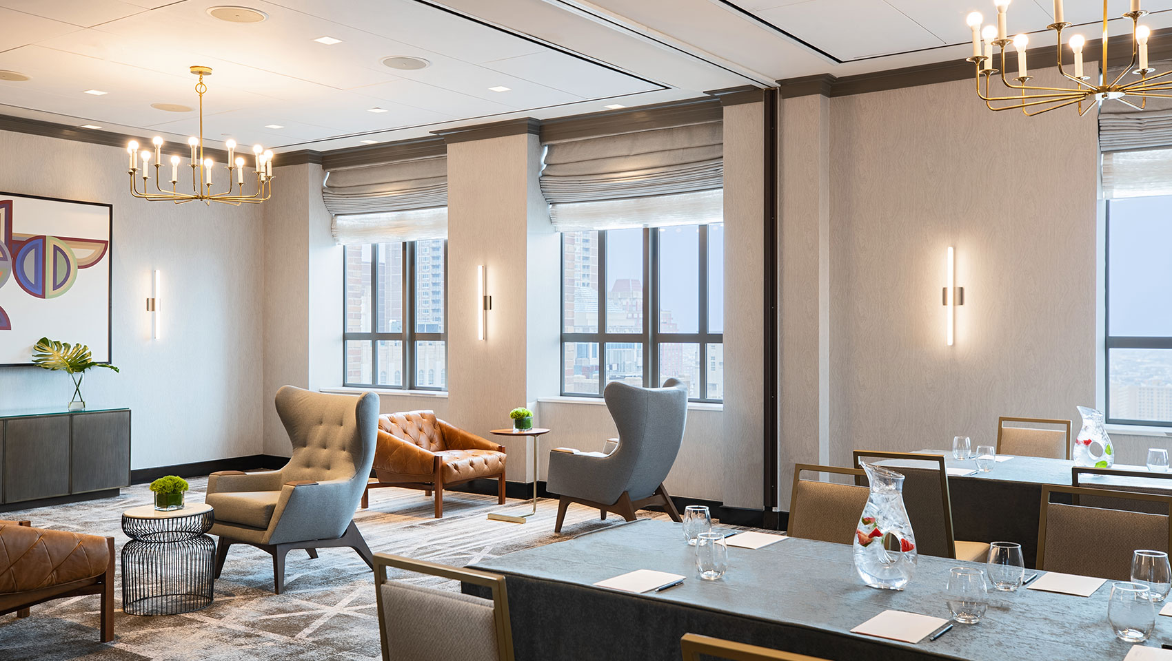Cret room at Kimpton Hotel Palomar Philadelphia in a brainstorm set up with a long table with notepads to one side and comfortable face-to-face chairs on the other, all encompassed within a room with multiple large windows and city views