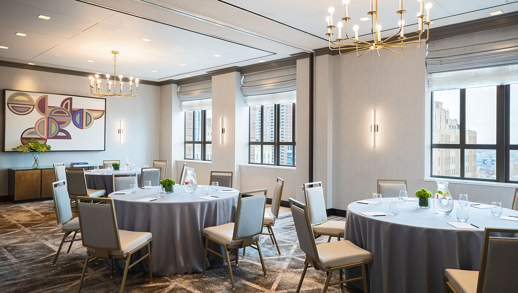 Cret room at Kimpton Hotel Palomar Philadelphia in a rounds meeting set up with multiple round tables that have notepads on top near large sunlit windows overlooking city views