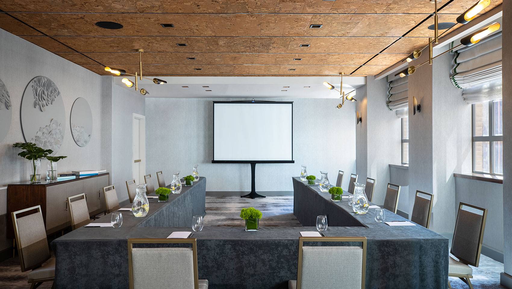 U-shape meeting set up in Tyng room located in Kimpton Hotel Palomar Philadelphia with tables set up in a U-shaped position and a presentation screen towards the back of the room in the center