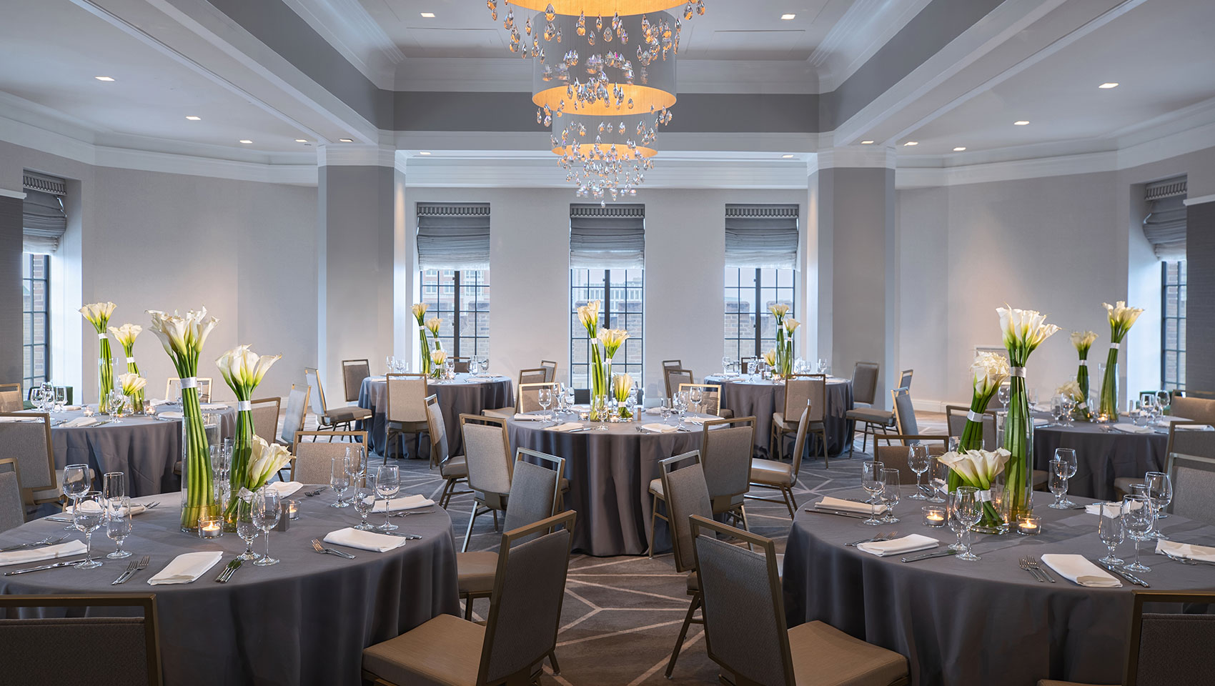 Kimpton Hotel Palomar Philadelphia ballroom set up for a social banquet with multiple round tables with floral arrangements placed in a sunlit room with surrounding windows overlooking views of the city