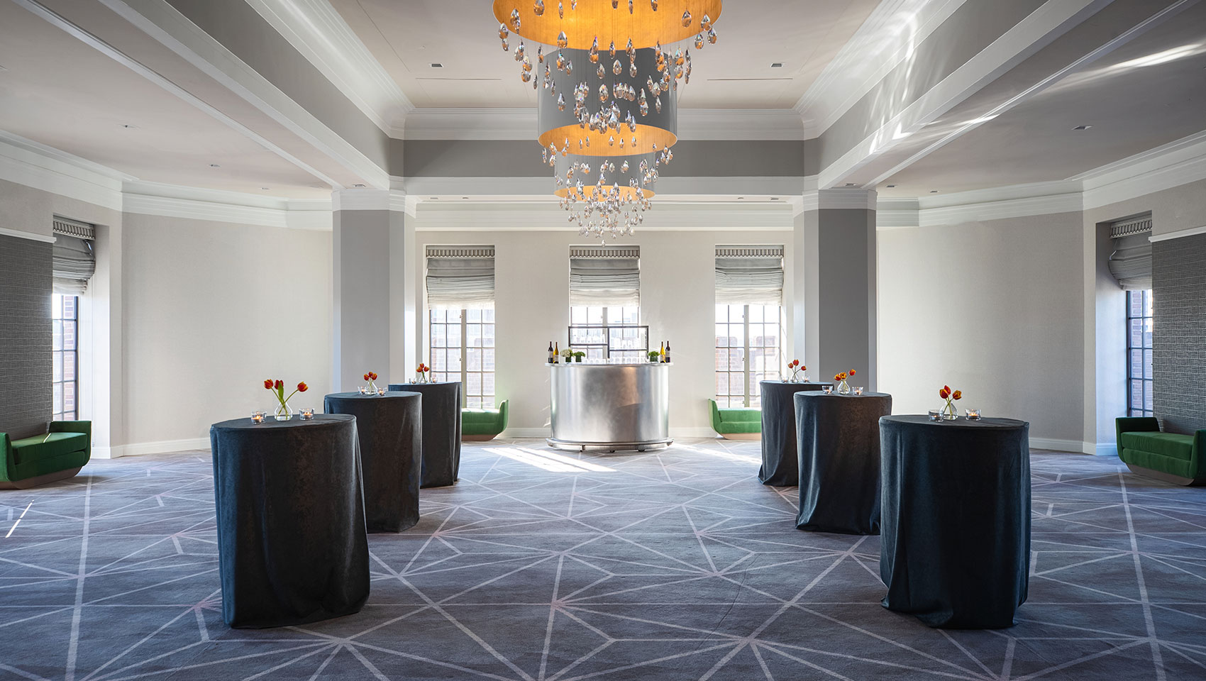 Ballroom social reception set up at Kimpton Hotel Palomar Philadelphia with cocktail tables throughout open area underneath circular chandeliers in the center of the room