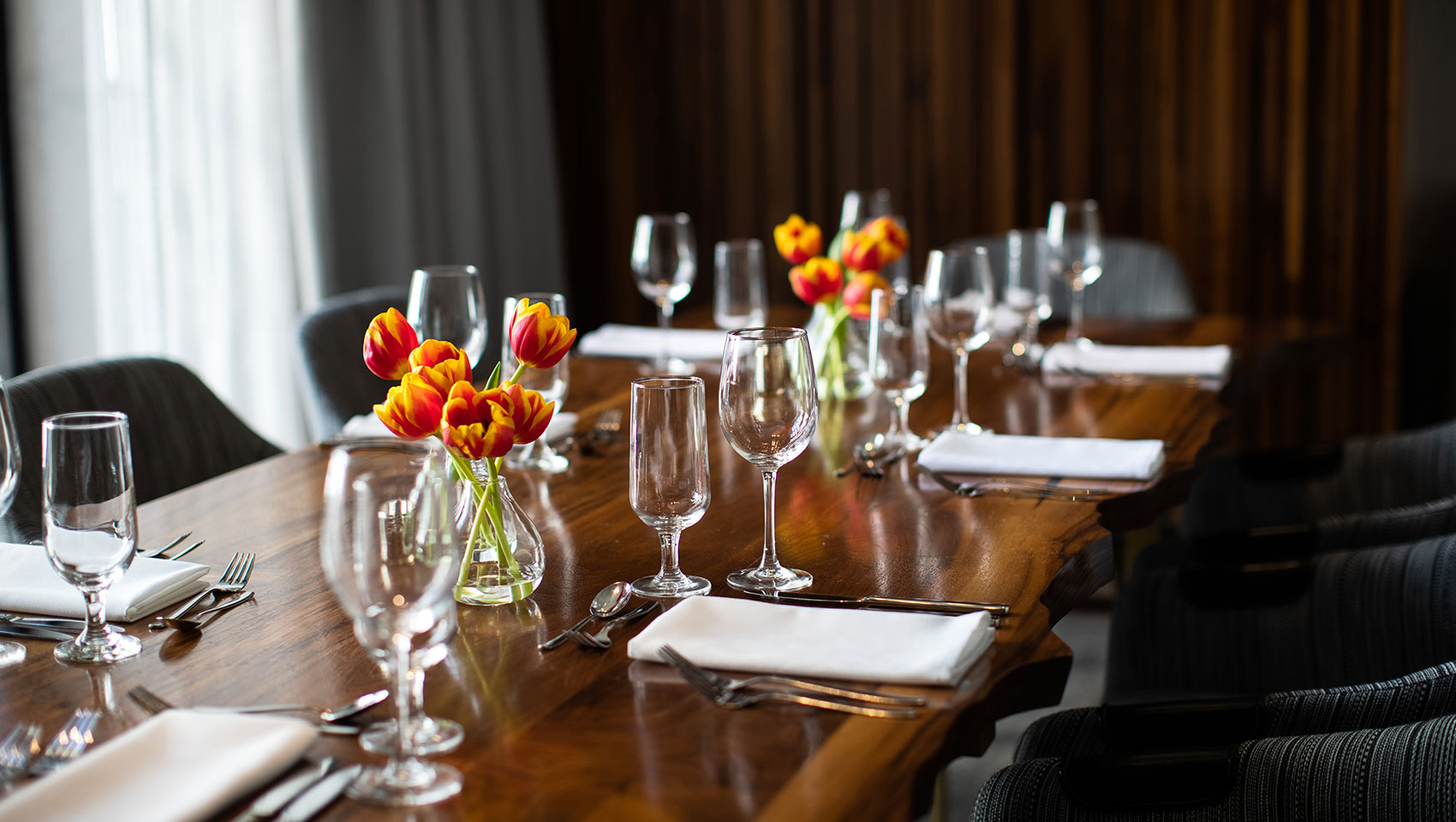 Private dining room set up in Calder room located in Kimpton Hotel Palomar Philadelphia glassware and floral arrangements in the center of a long wood table with chairs surrounding