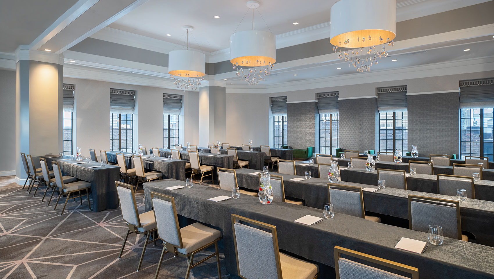 Classroom setup at Kimpton Hotel Palomar Philadelphia's ballroom showing long tables with notepads all facing the same direction within a room surrounded with windows that overlook city views