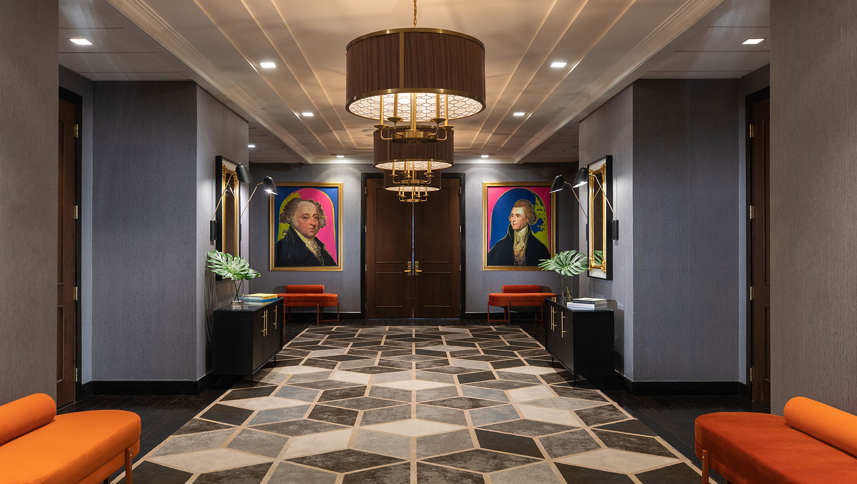 Kimpton Hotel Palomar Philadelphia 24th floor meeting + event foyer area showing geometric carpet in open area, brightly colored plush seating, and a series of circular lighting fixtures