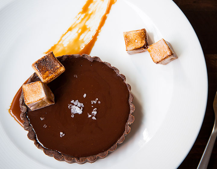Chocolate dessert with toasted marshmallows on a plate next to a cup of coffee