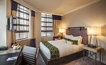 City view queen room with queen bed and two adjacent nightstands situated amongst two large windows with views of the city