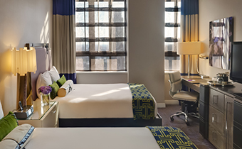 Accessible queen queen room with two queen beds next to two large sunlit windows overlooking city views