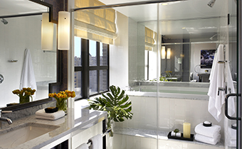 City view king spa bathroom with expansive countertop space and a large stand in shower with a bench and sunlit window