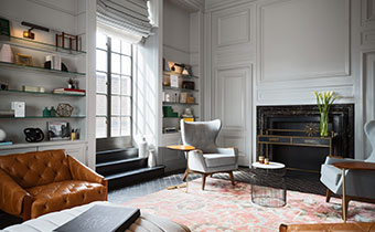 Kimpton Hotel Palomar Philadelphia Aia Library showing accent chairs surrounding a fireplace with bookshelves on background wall with large sunlit windows