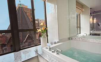 Spa king room bathroom with large soaking tub, countertop flowers in a vase, and a large window