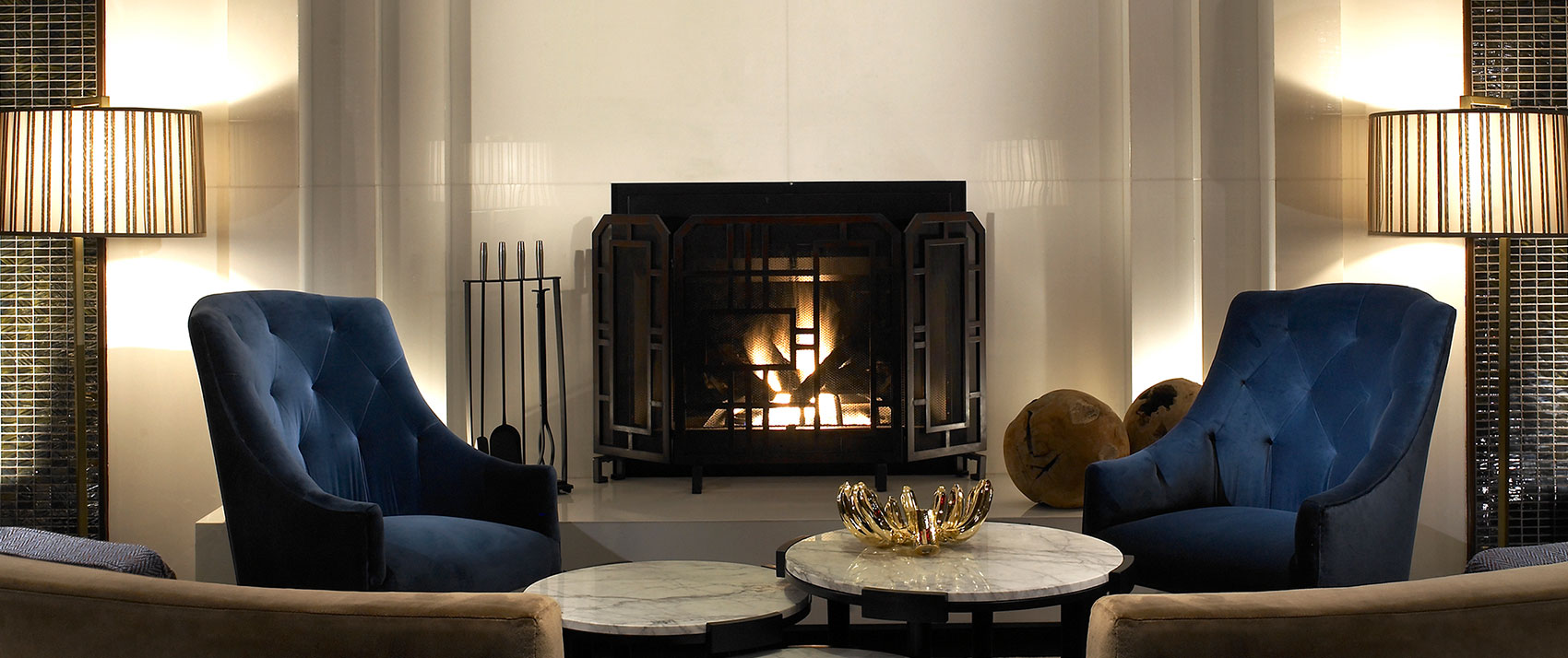 Kimpton Hotel Palomar Philadelphia lobby living room with seating, circular marbletop coffee tables, and a fireplace