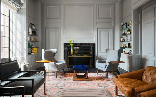 Kimpton Hotel Palomar Philadelphia's AIA Library with seating, bookshelves, and fireplace